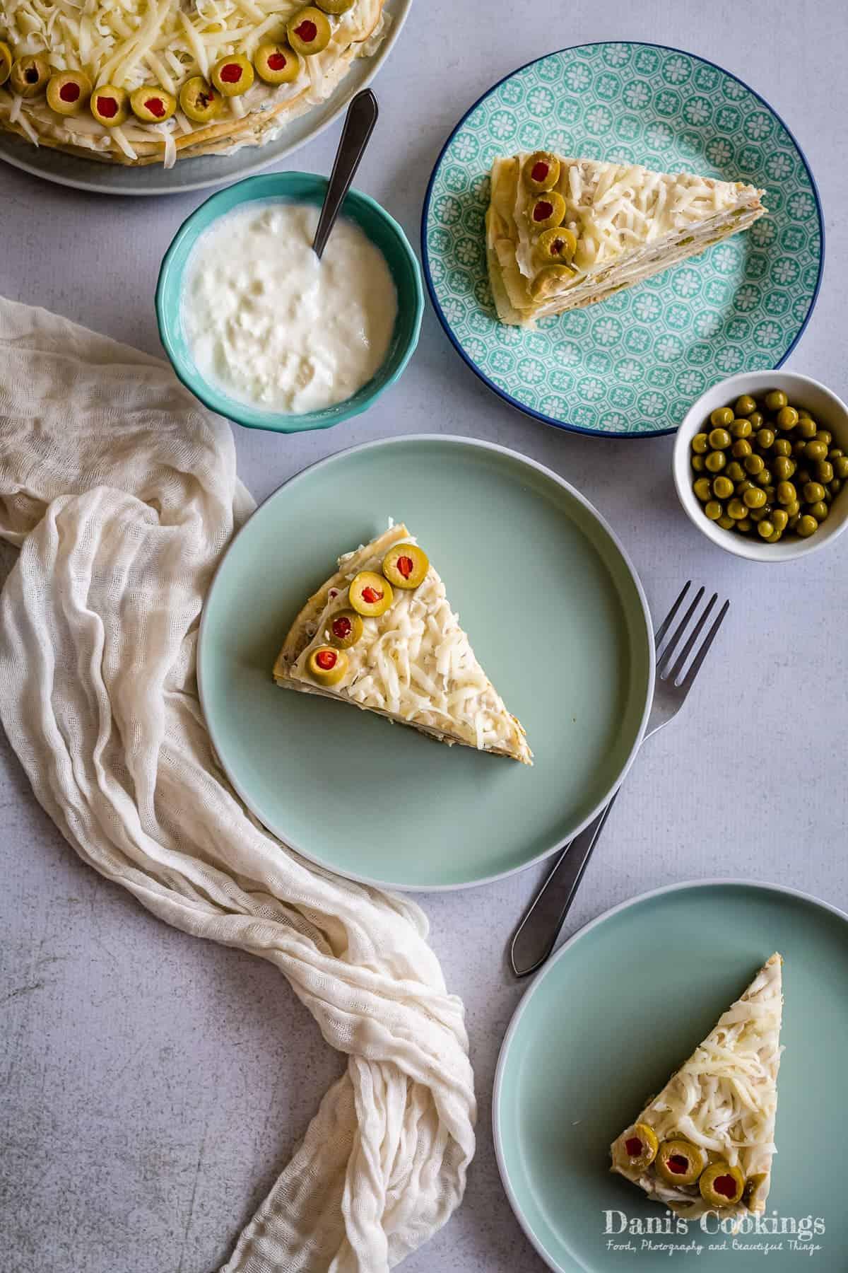 a flat lay of crepe cake slices around peas and yogurt