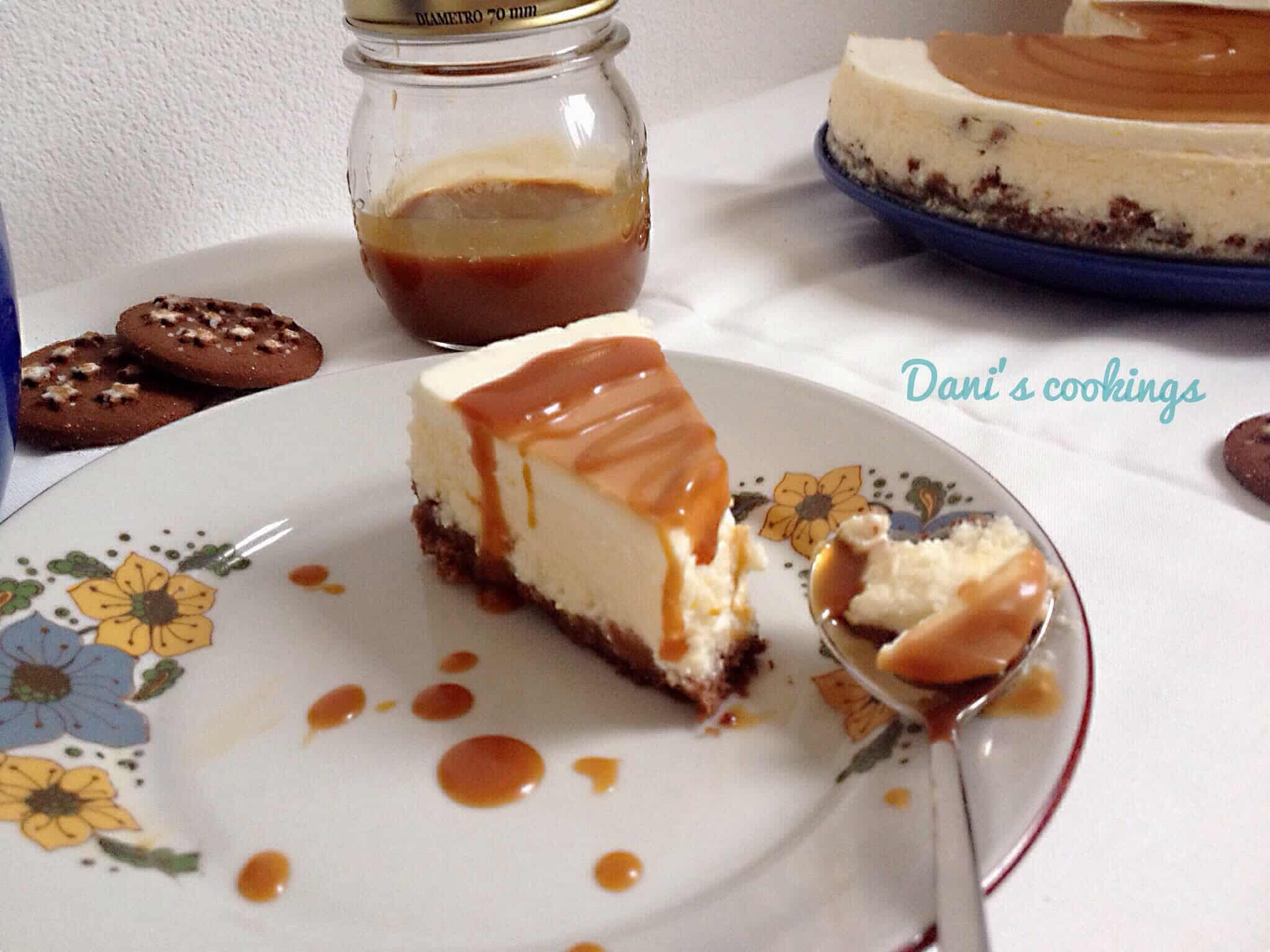 a slice of cheesecake with caramel next to it and cookies aside