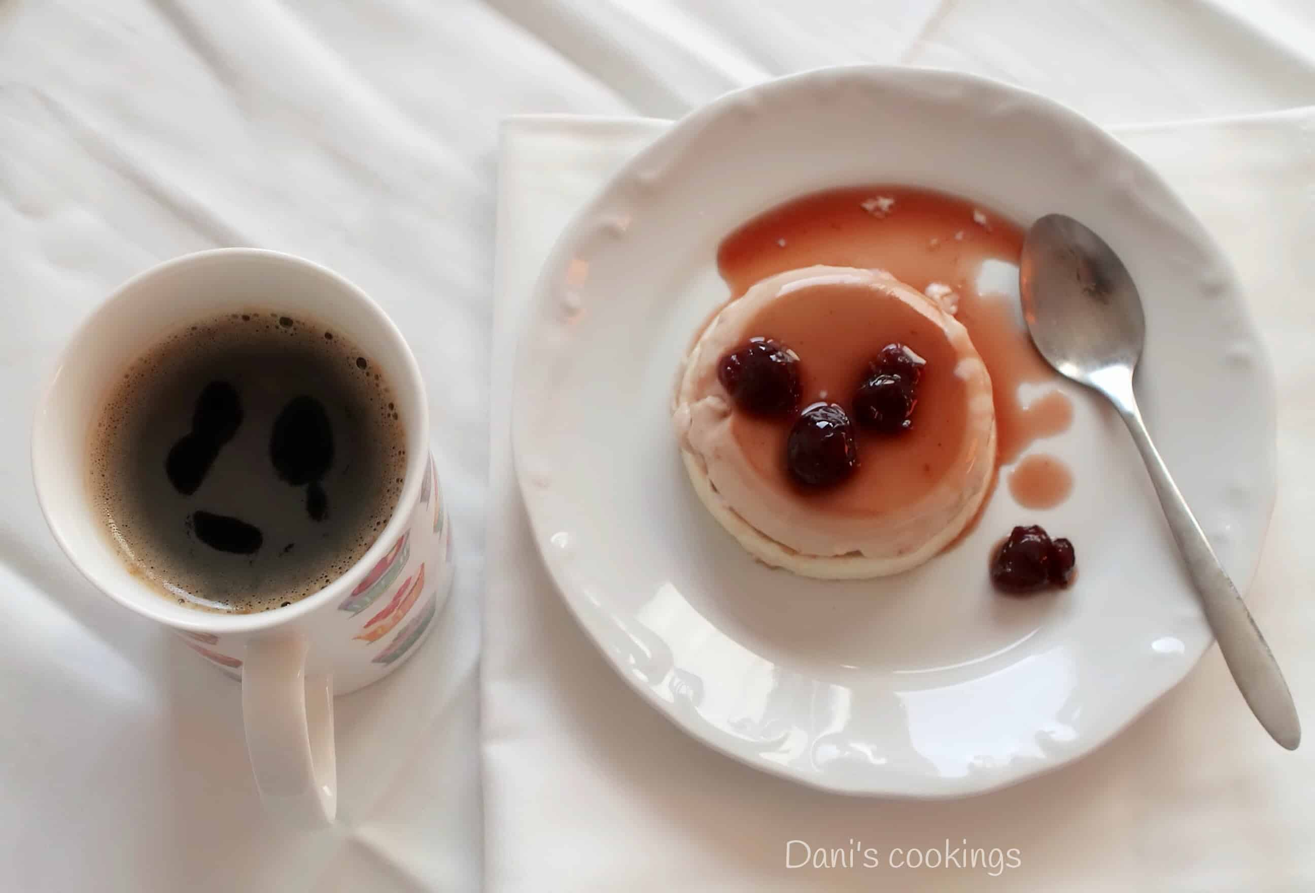 panna cotta with jam on a plate and a cup of coffee on a side