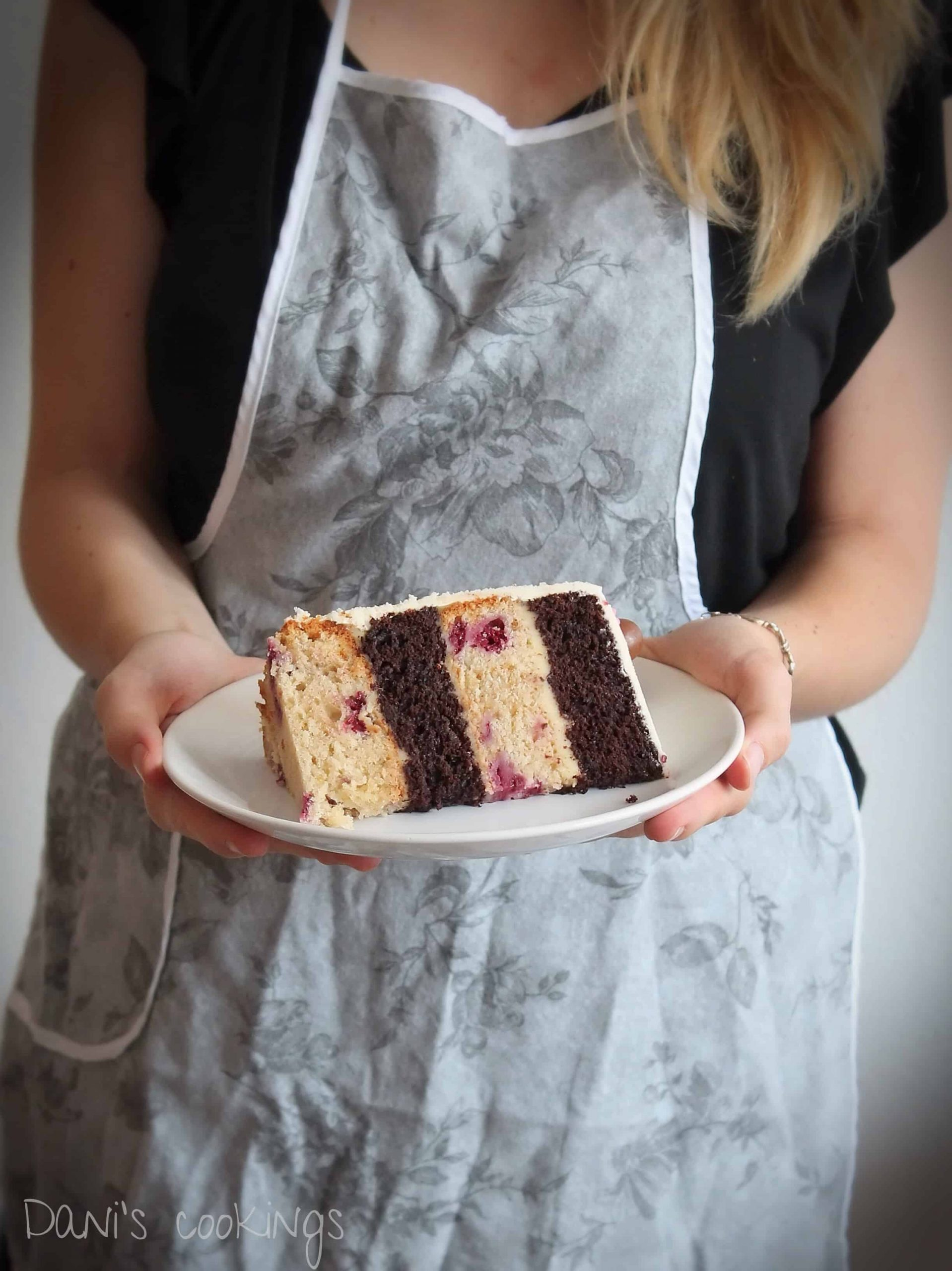 a woman holding a slice of layer cake