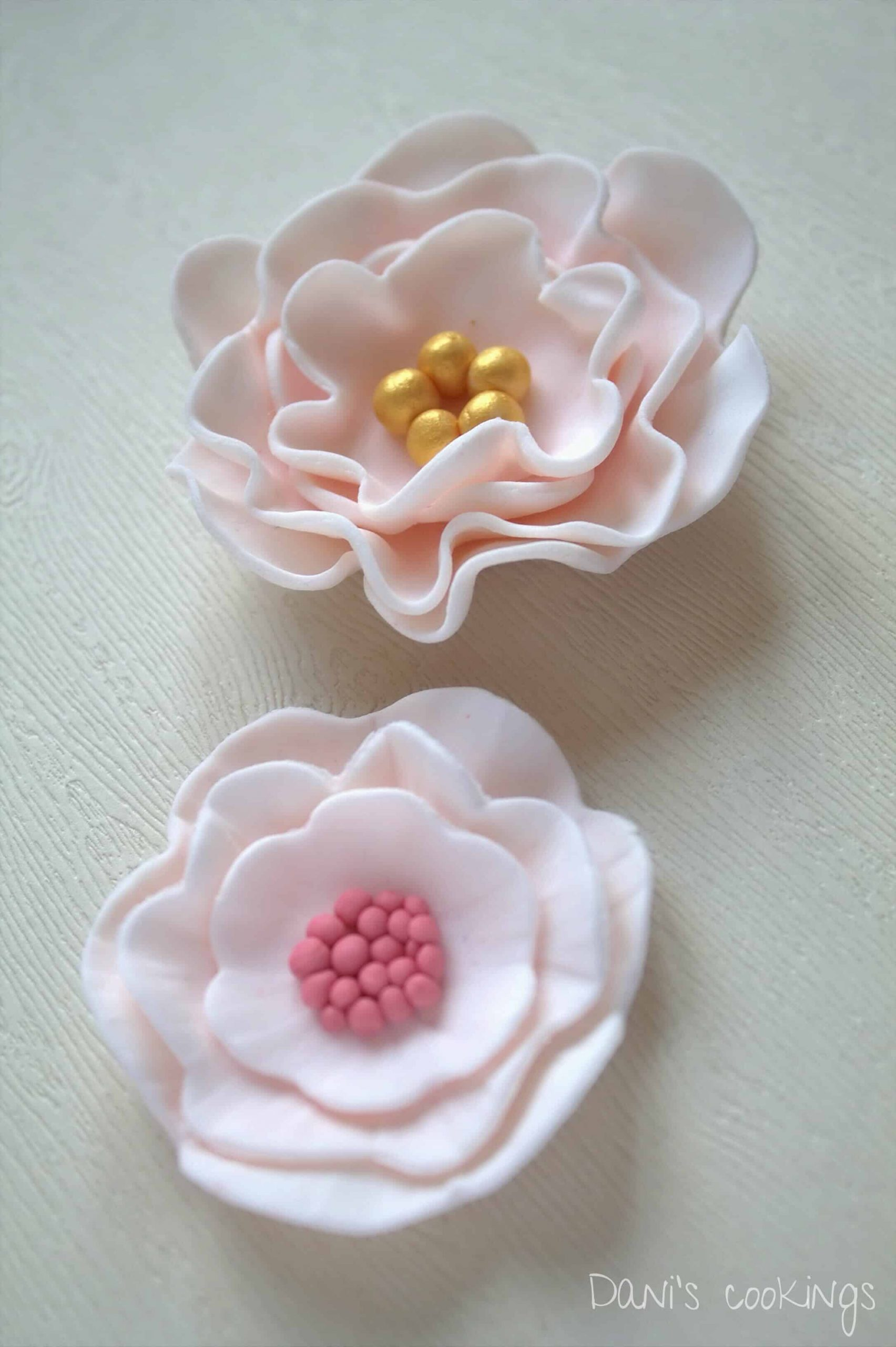 two fondant flowers on a wooden surface