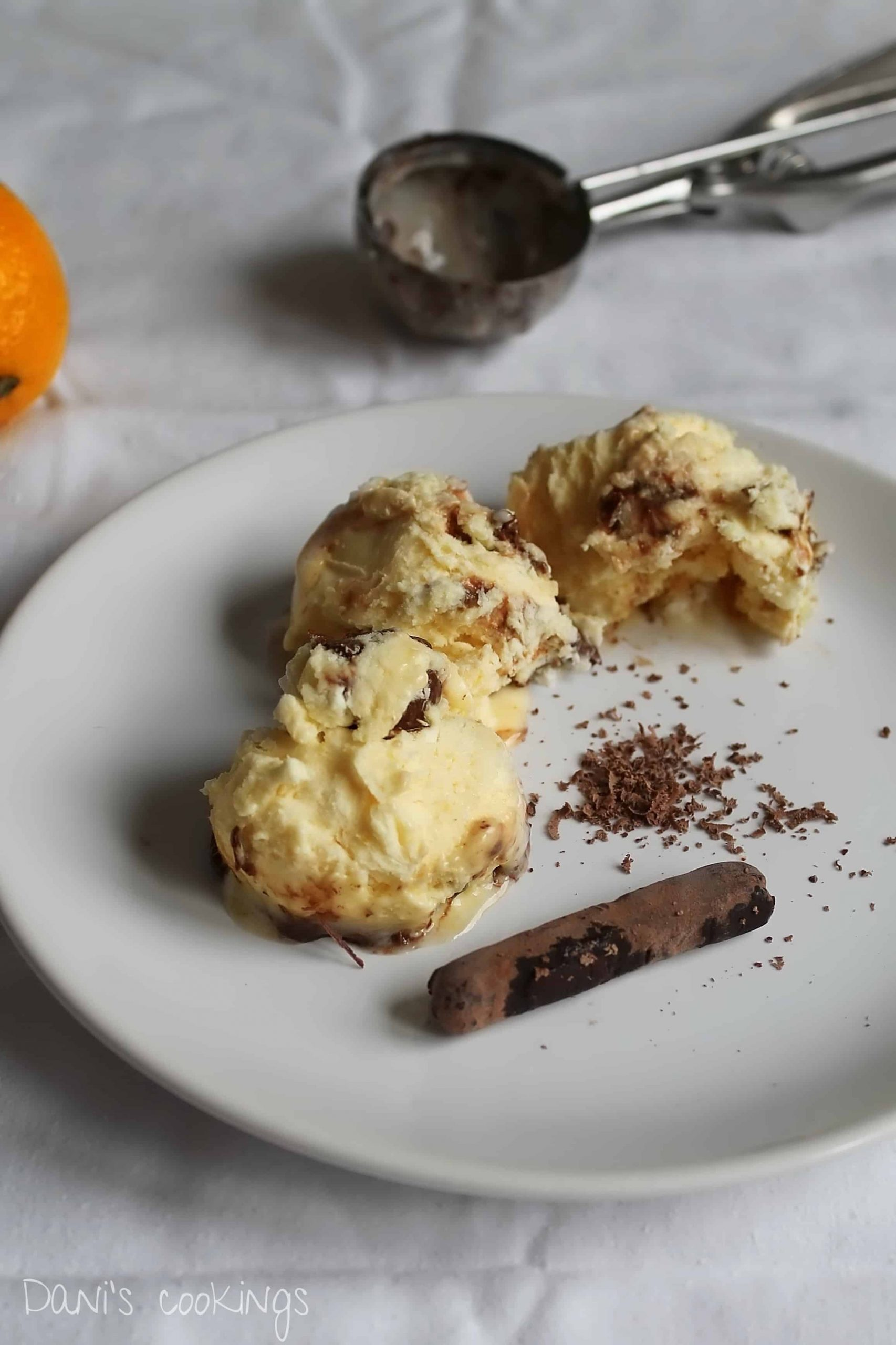 three scoops of semifreddo on a plate with an ice cream spoon and lemon aside