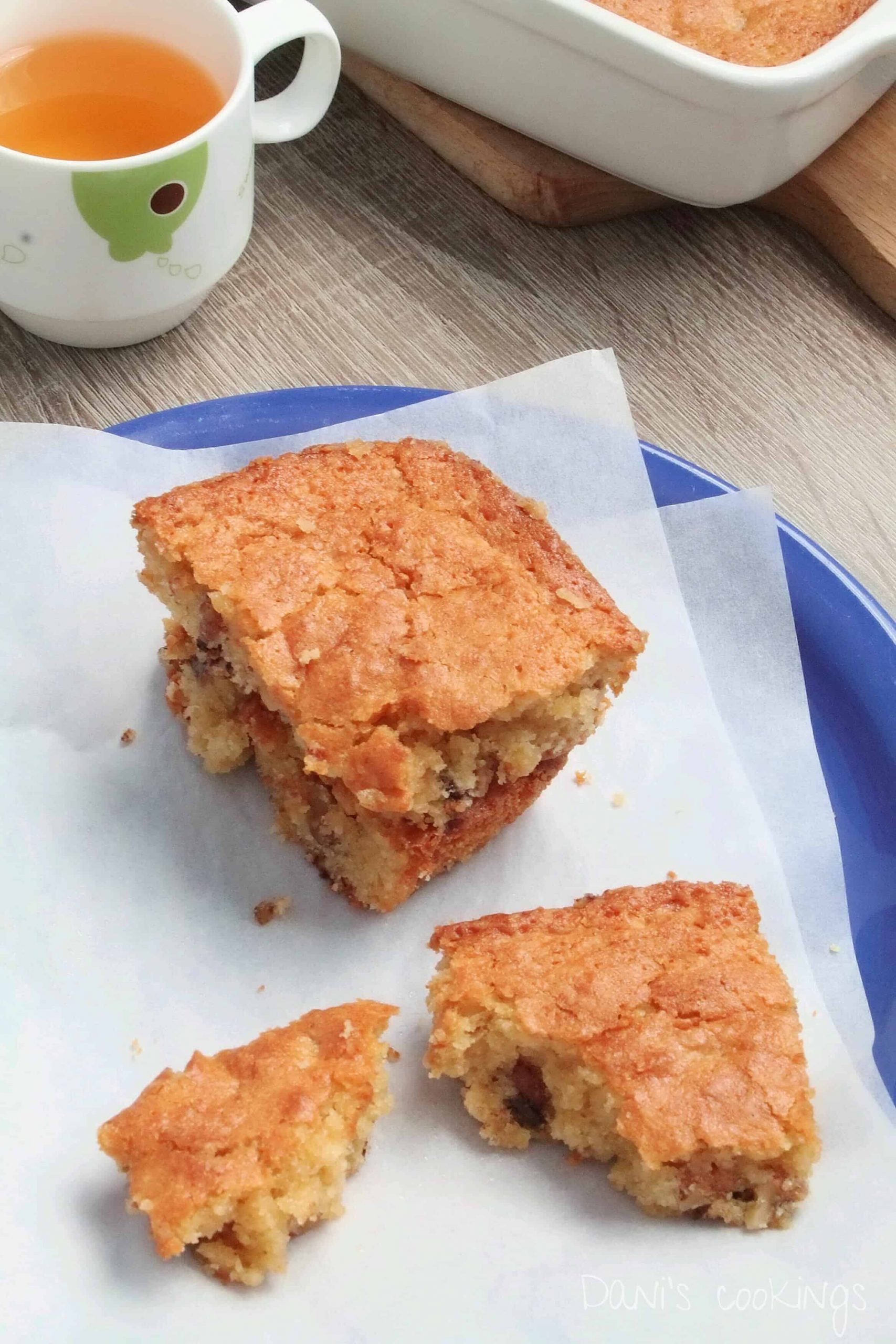 blondies on a plate, one broken, with tea aside