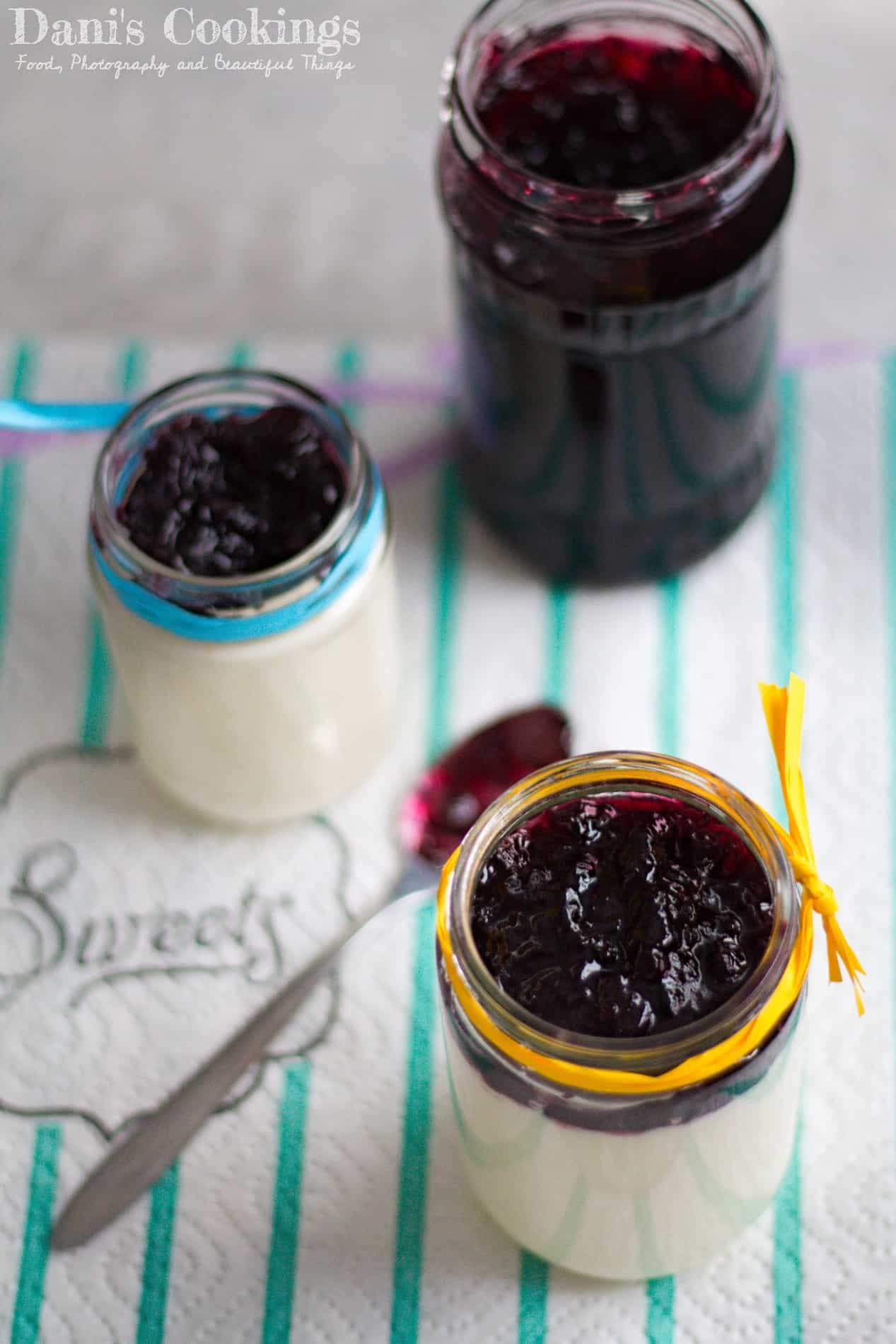 panna cotta with blueberry jam in jars and a jar of jam aside