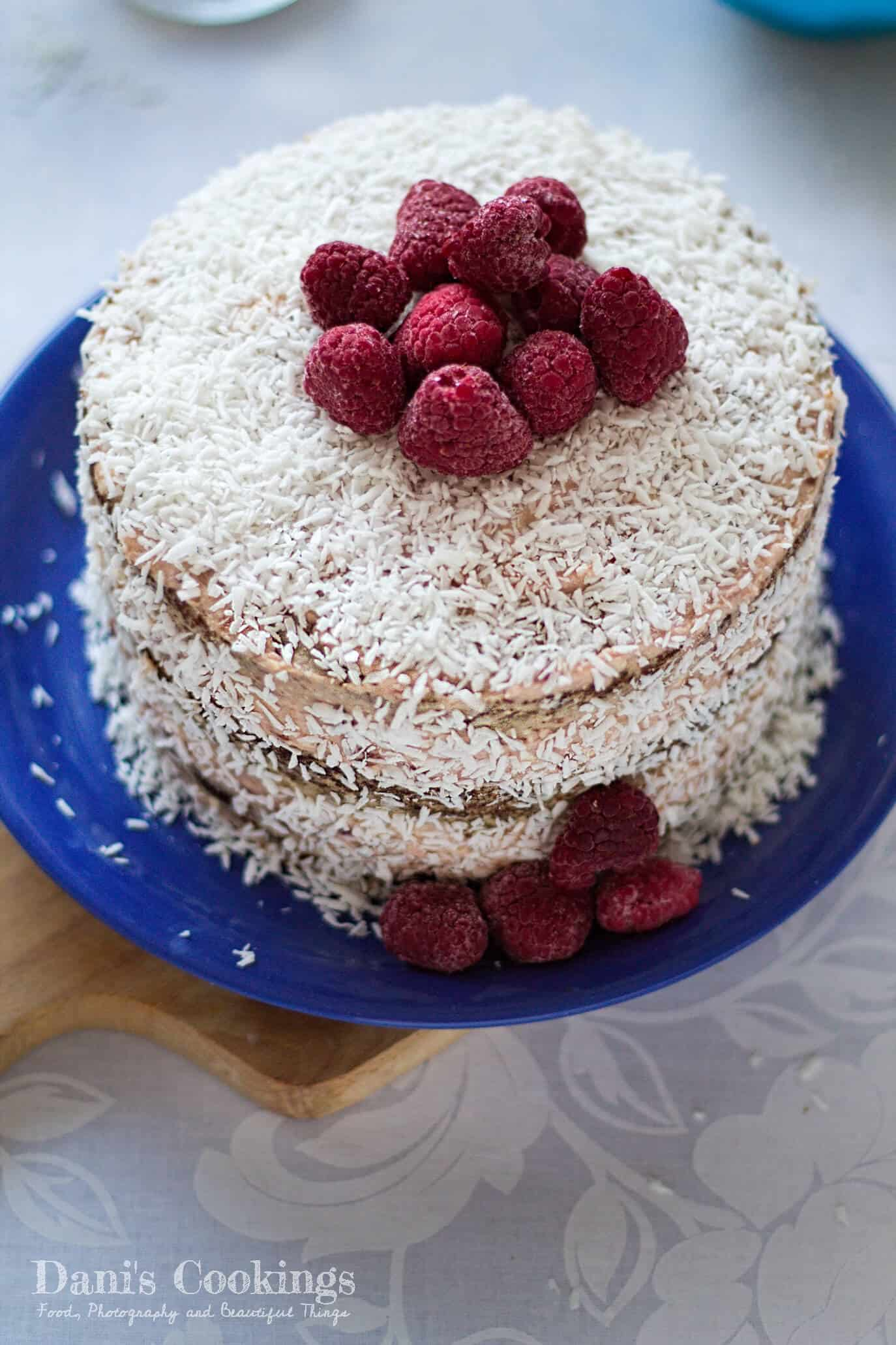 a layer cake with shredded coconut and raspberries