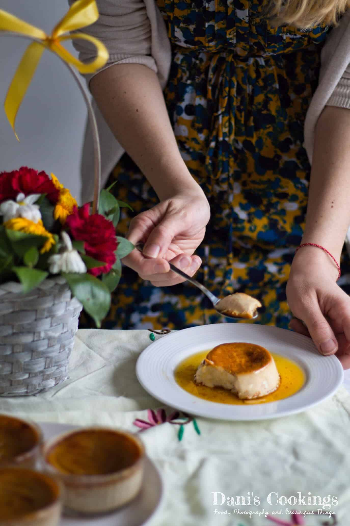 a woman eating creme caramel from a plate