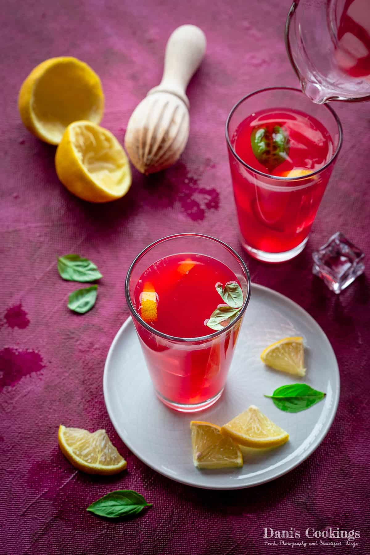 two glasses of pink lemonade with squeezed lemons and basil