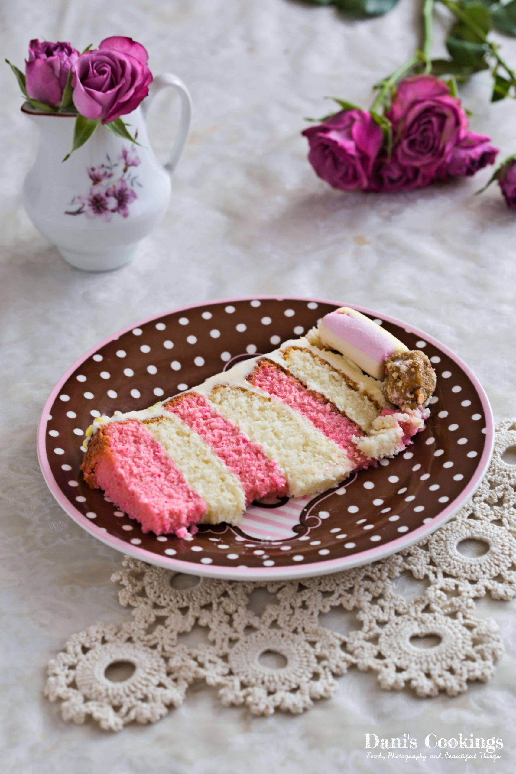 a slice of vanilla cake with pink and yellow layers on a plate with roses aside