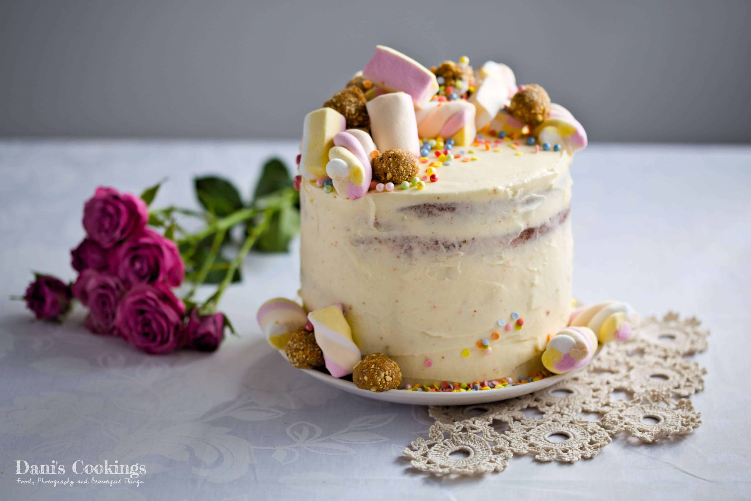 decorated vanilla cake with pink roses aside