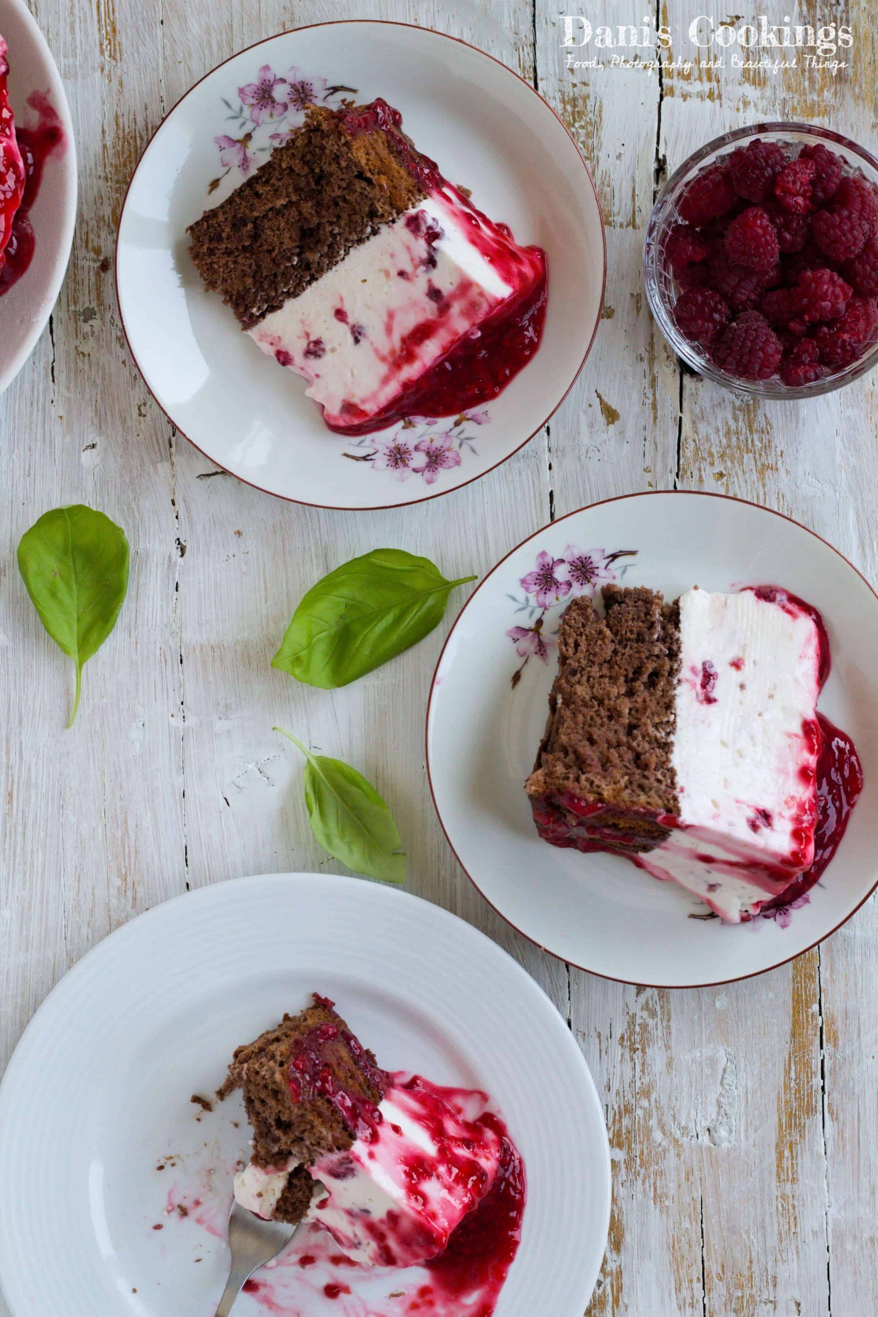 three slices of raspberry cheesecake on a table, one eaten