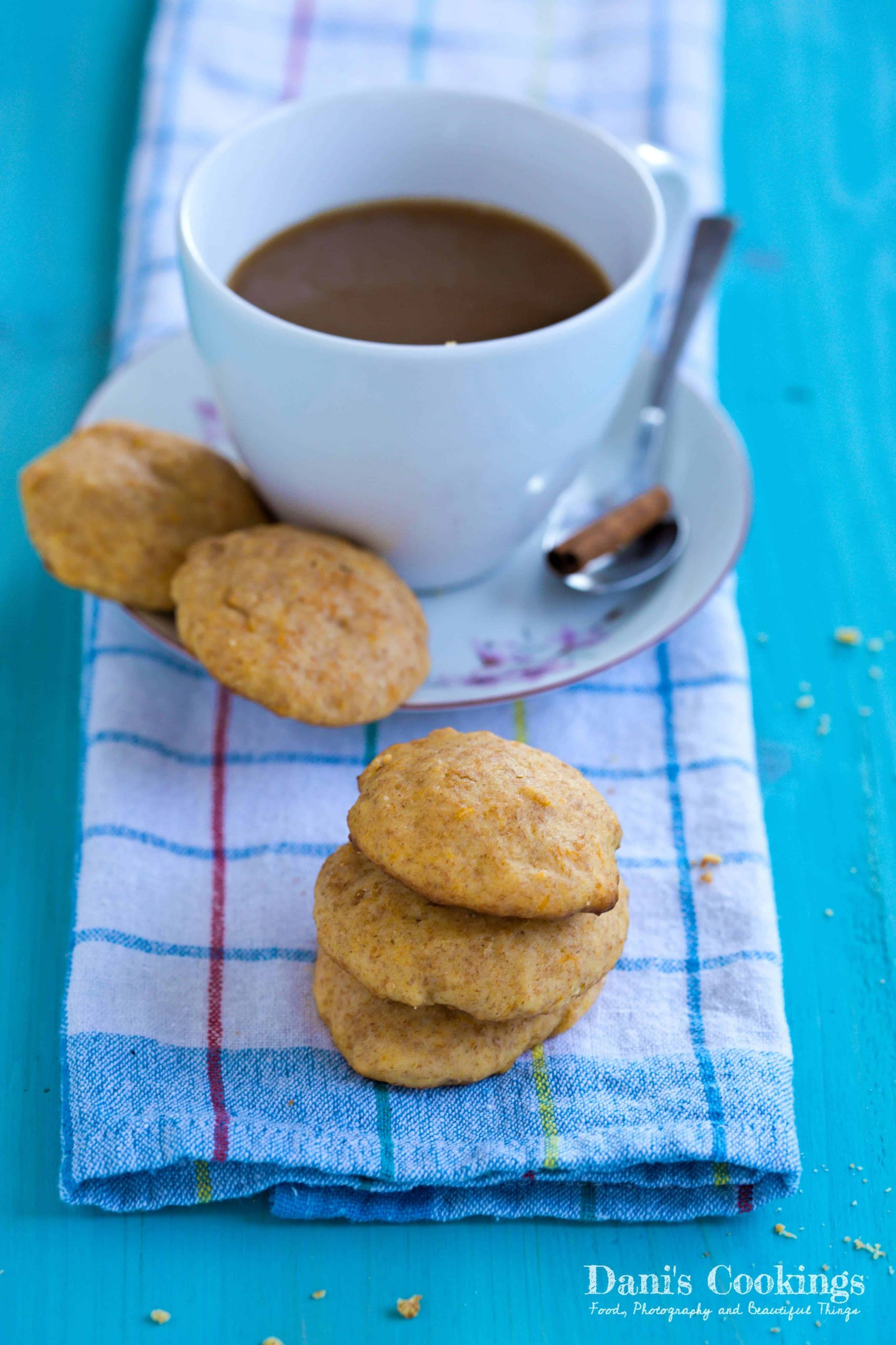 a cup of coffee with cookies aside