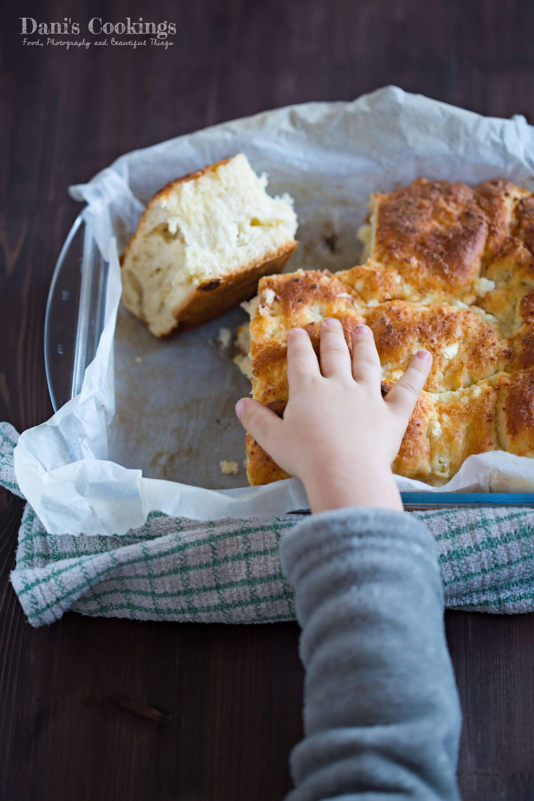 cut and crumbled cheese bread with a kid's hand on top