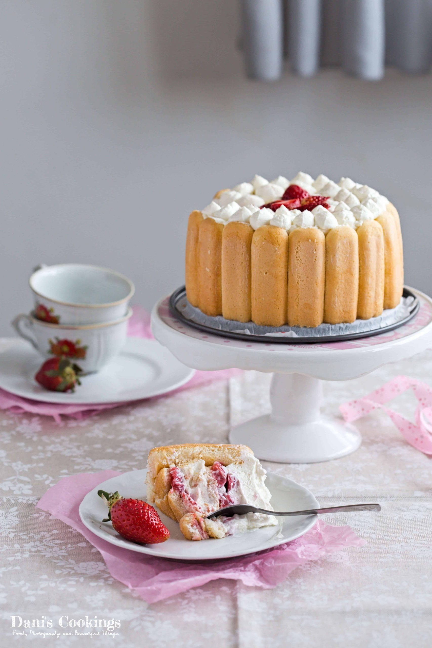 a slice of strawberry charlotte next to the whole cake