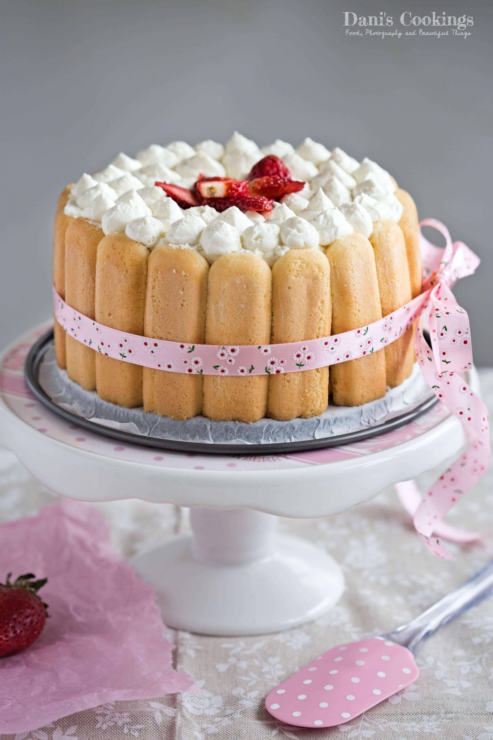 strawberry charlotte on a pink cake stand with a spatula aside