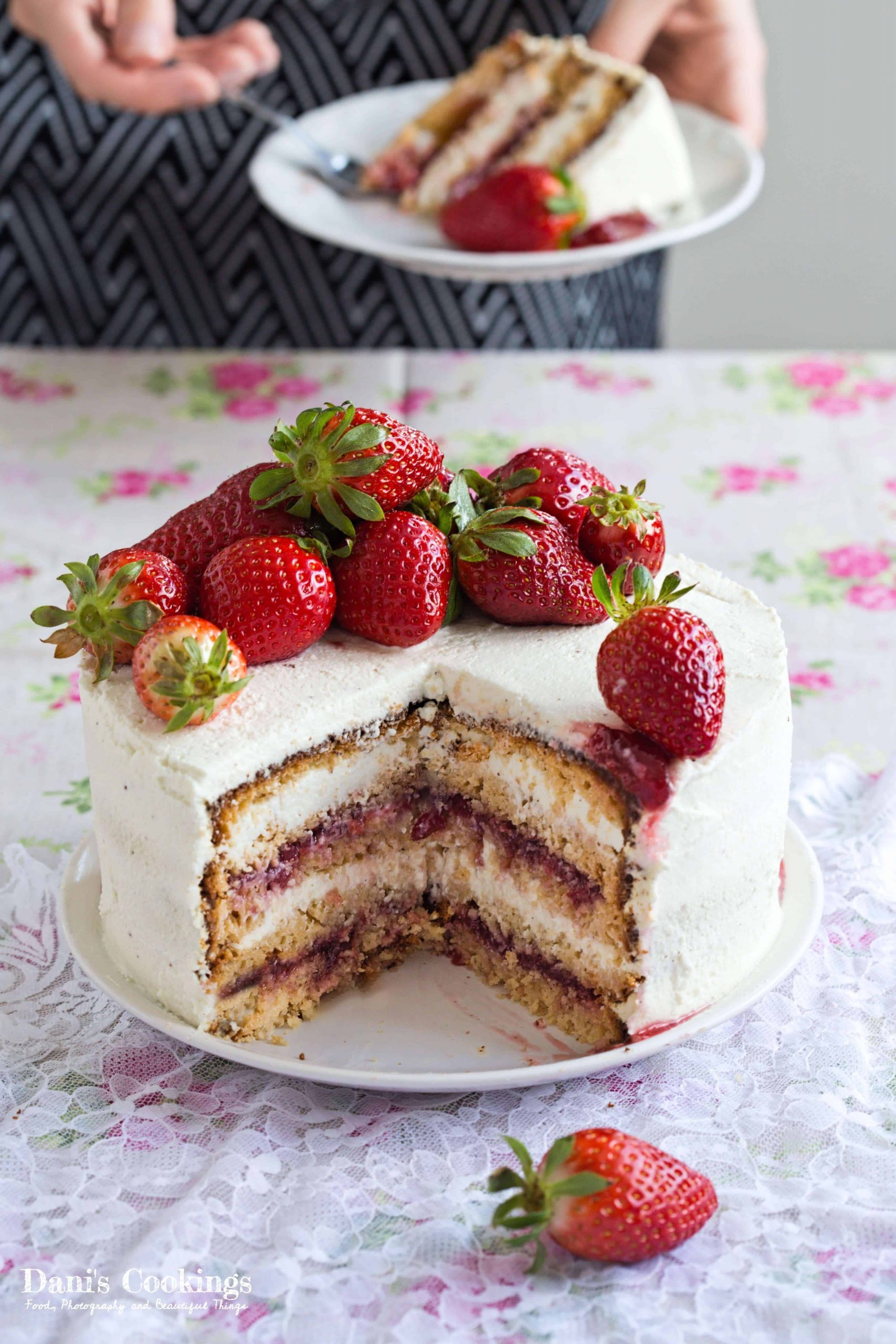 a woman eating a slice of cake behind the whole cake