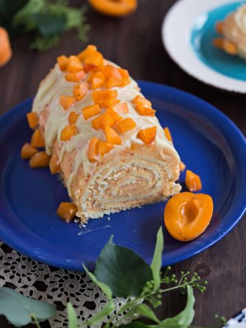 Delicious vanilla cake roll with fluffy apricot buttercream frosting covered by white chocolate glaze and fresh apricots - a wonderful dessert for every occasion!