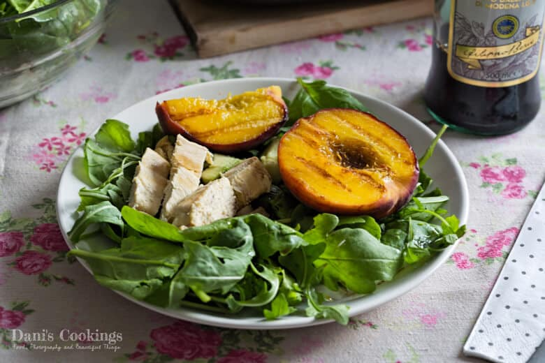 Grilled Peach Salad with Chicken and Avocado, served on a plate and with balsamic vinegar bottle on a side