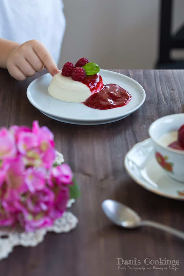 a chid touching a panna cotta in a plate