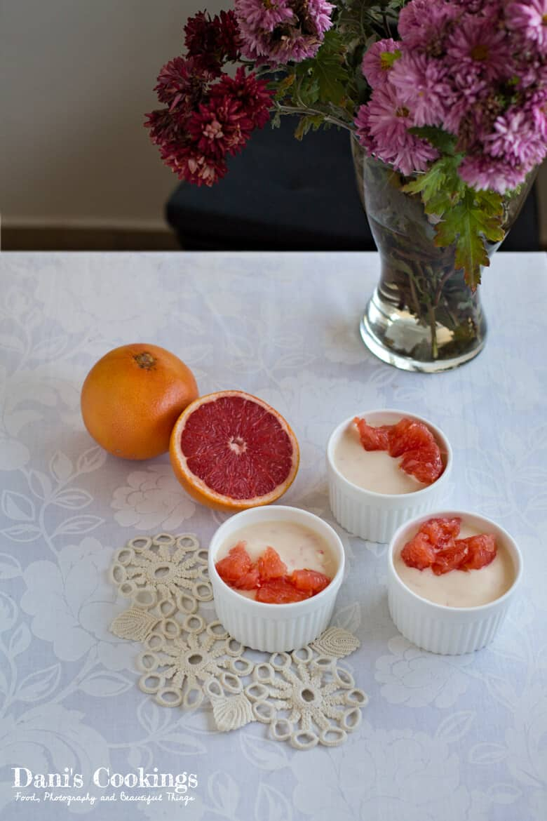 ramequins with dessert next to grapefruits and a vase of flowers