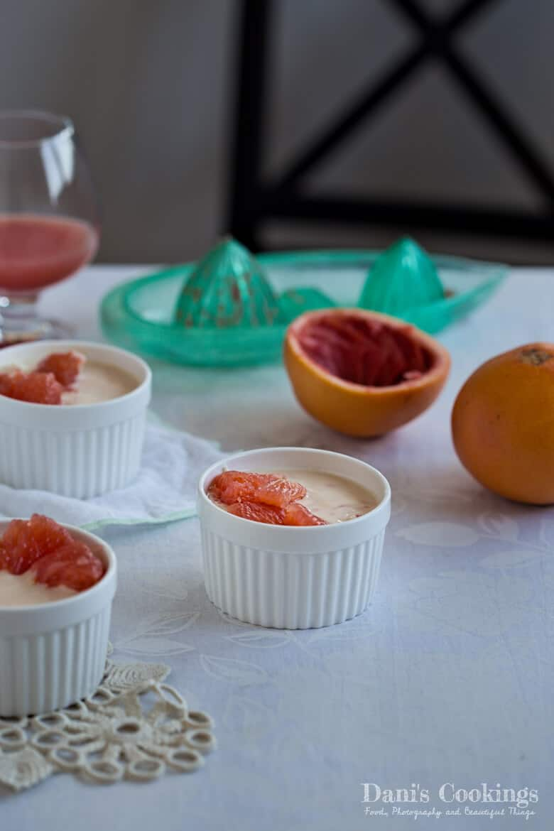 a grapefruit dessert on a table with ramequins, grapefruit and a glass