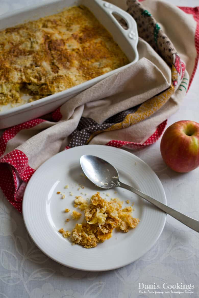 a dump cake next to a plate with a spoon and an apple
