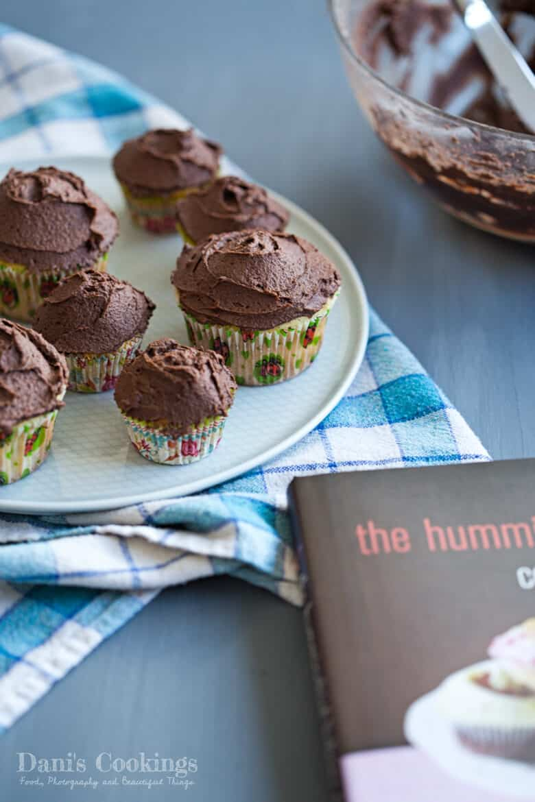 cupcakes with chocolate frosting on a plate next to a cookbook