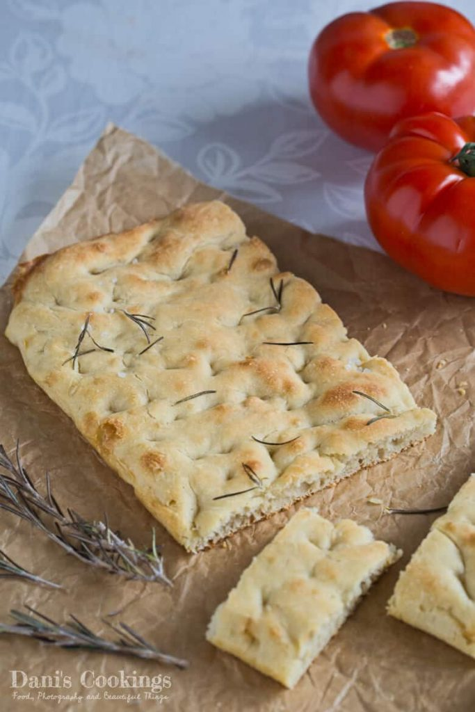 Focaccia bread on a table with tomatoes on the side