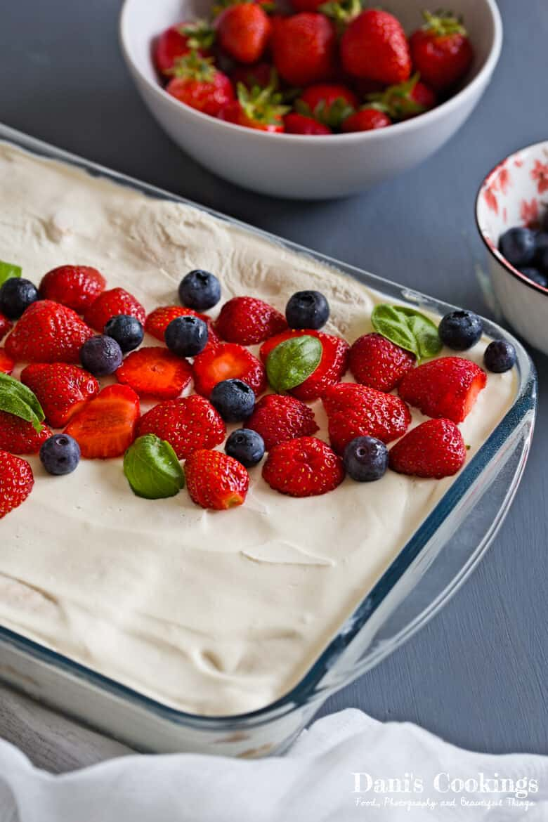 No Bake Berry Ice Box Cake on a table with fruits on a side