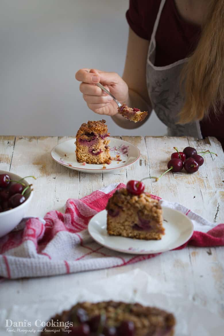 a woman eating a slice of crumble cake