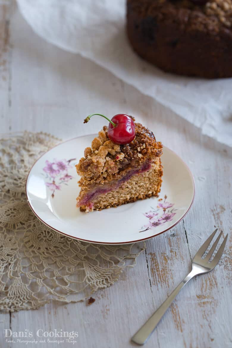 a slice of crumble cake with cherry on top