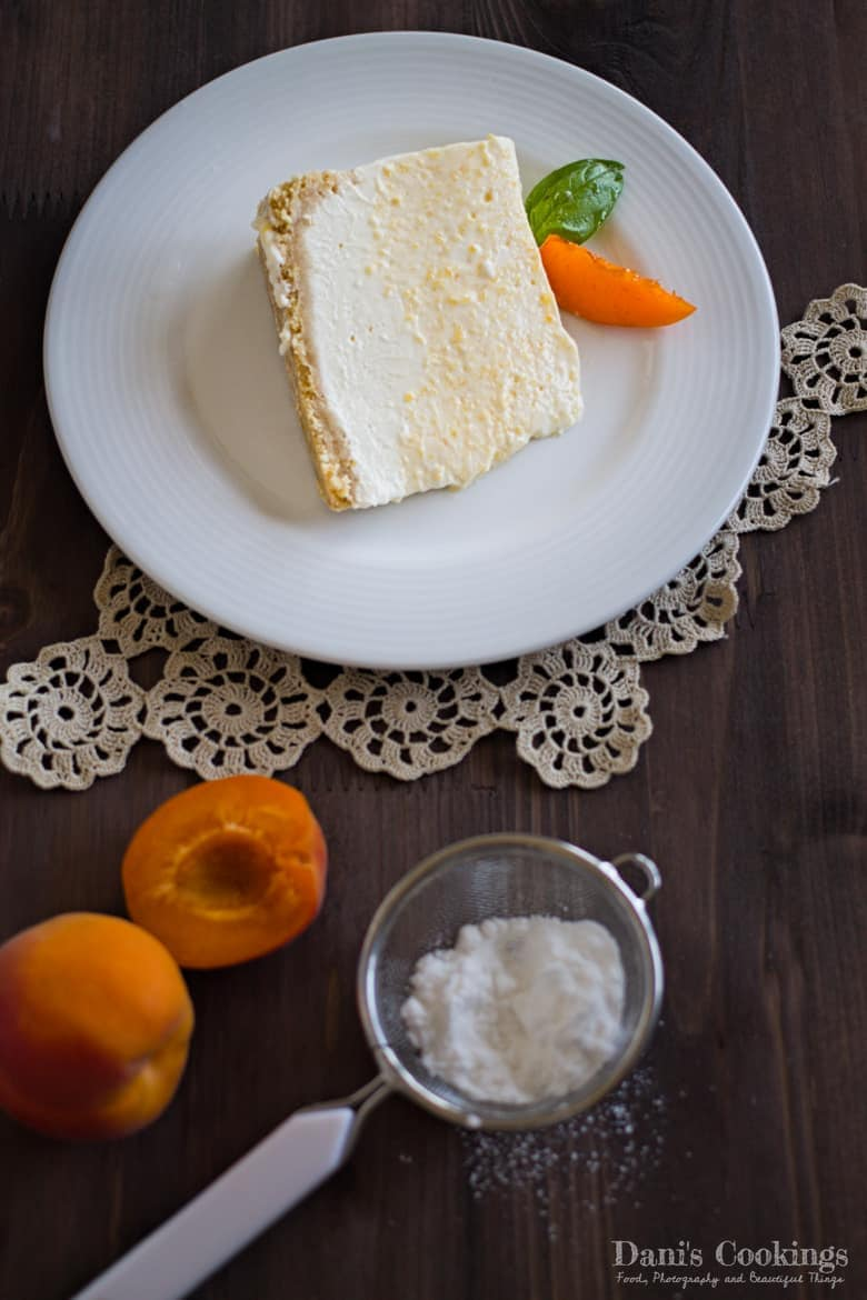 a slice of cheesecake with posdered sugar aside