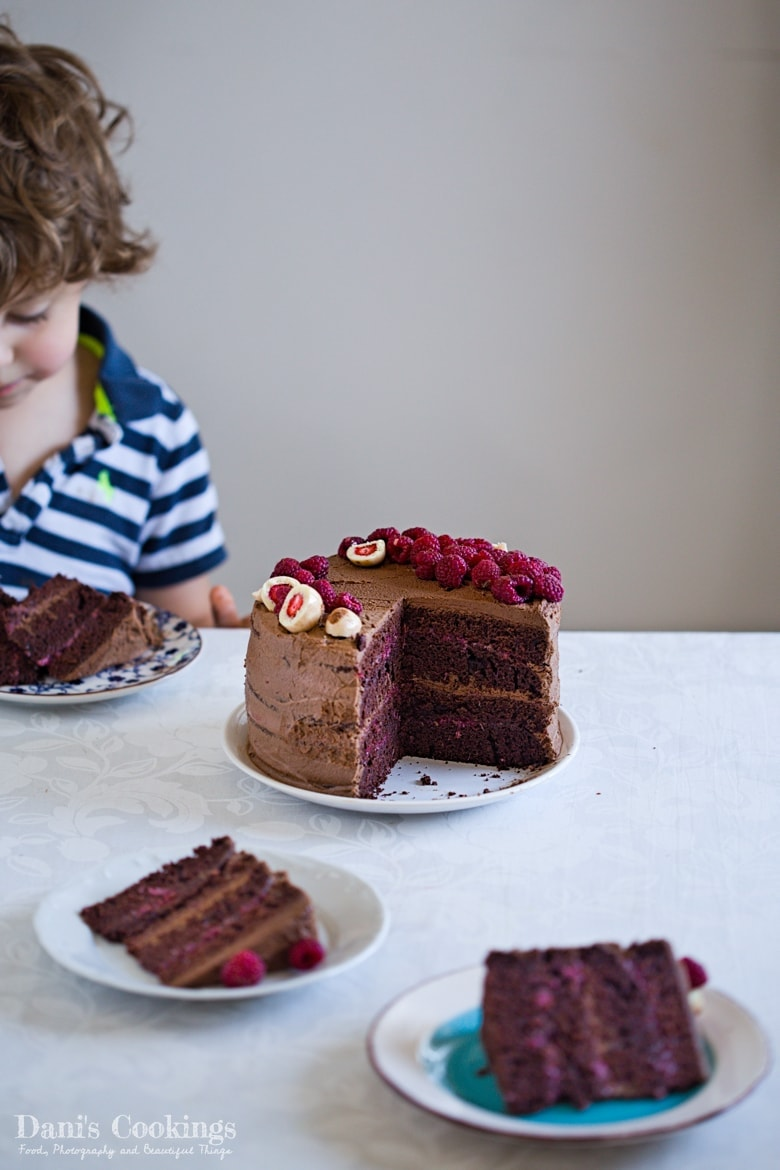 a child eating chocolate cake next to the sliced cake