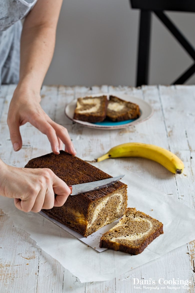 Cutting a Cream Cheese banana Bread on a wooden table