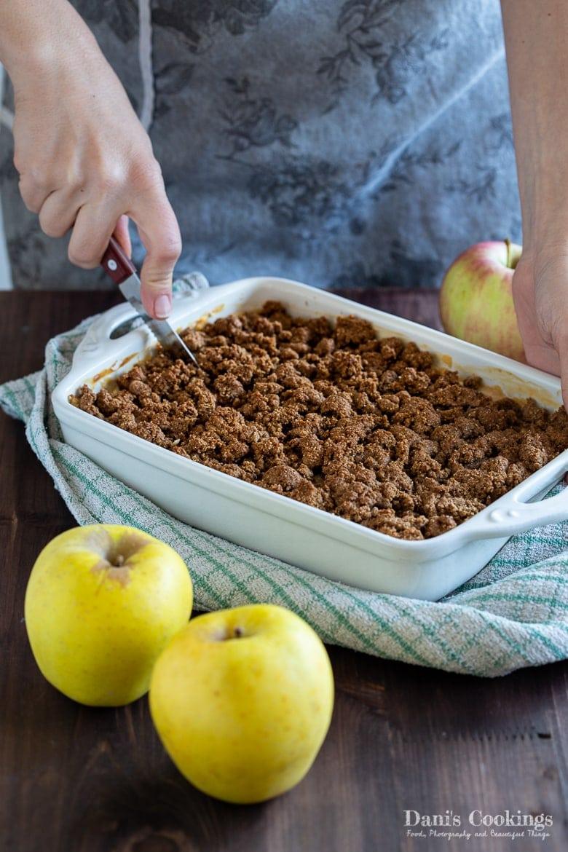 a woman cutting Sour Cream Apple Crumb Cake