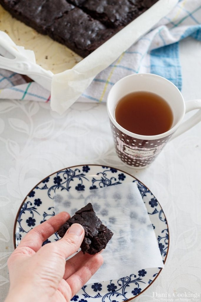 vegan black bean brownie in a hand with a cup of tea