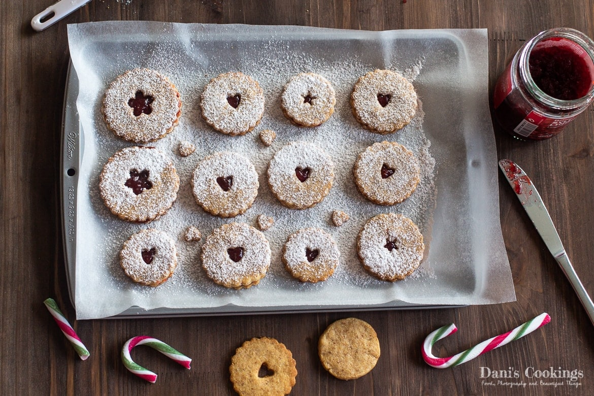 a pan with linzer cookies sprinkled with powdered sugar