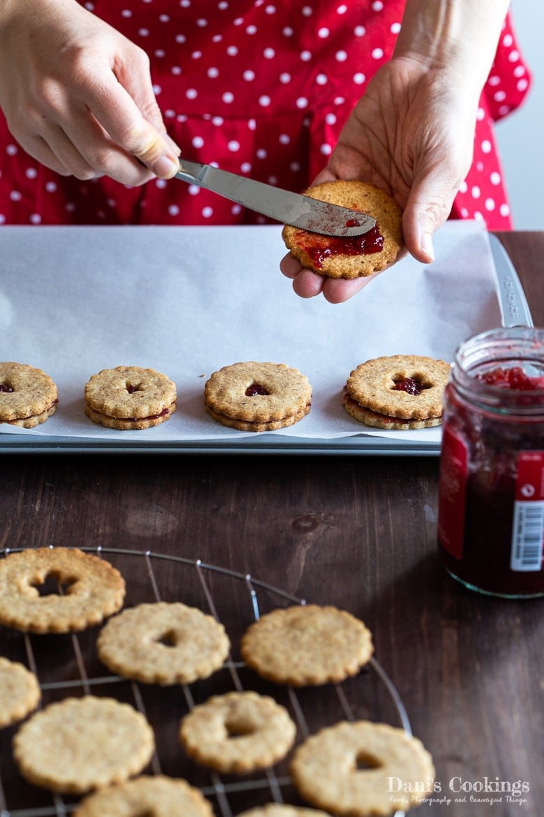 a woman adding jam on a linzer cookie
