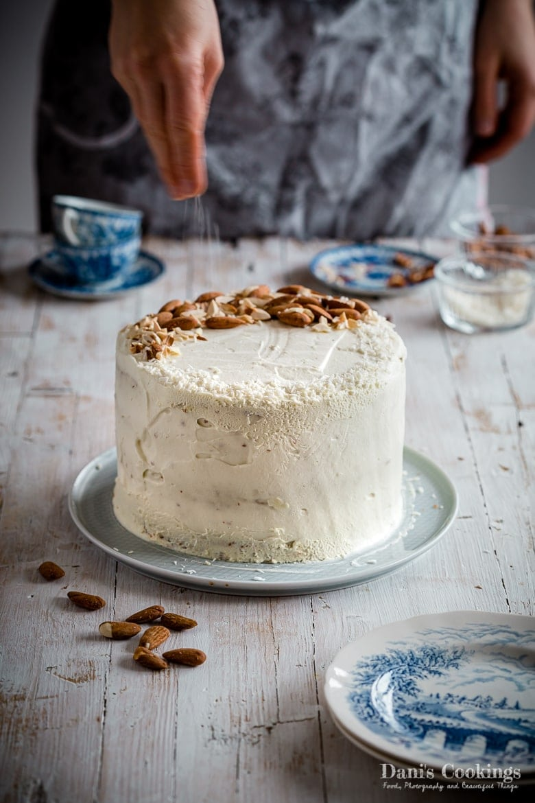 a woman sprinkling a white cake with almonds