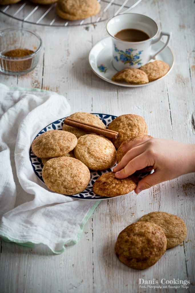 Easy Snickerdoodle Cookies in a plate with someone taking from them
