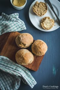 Fluffy Einkorn dinner rolls served on a wooden board and one cut on a plate