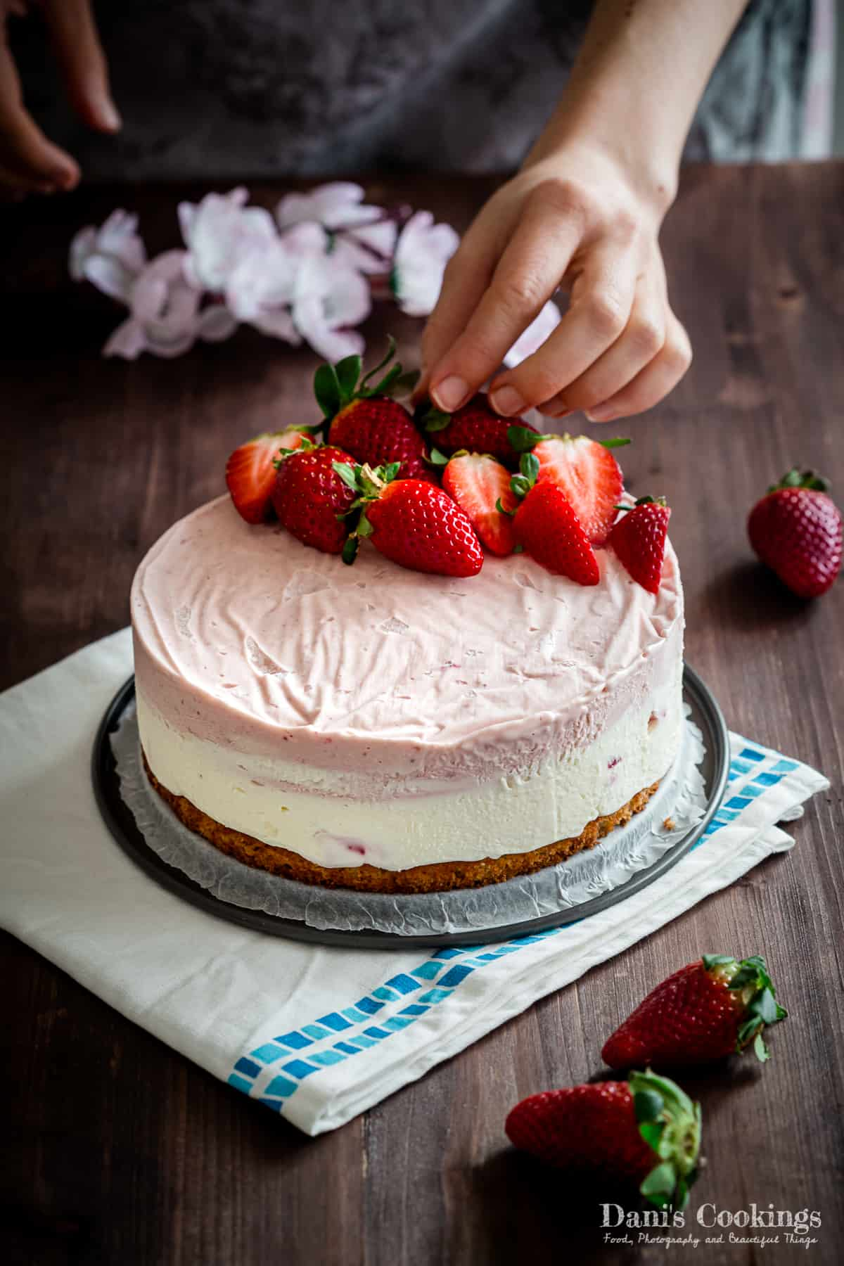 a woman decorating a frozen cake with fresh strawberries