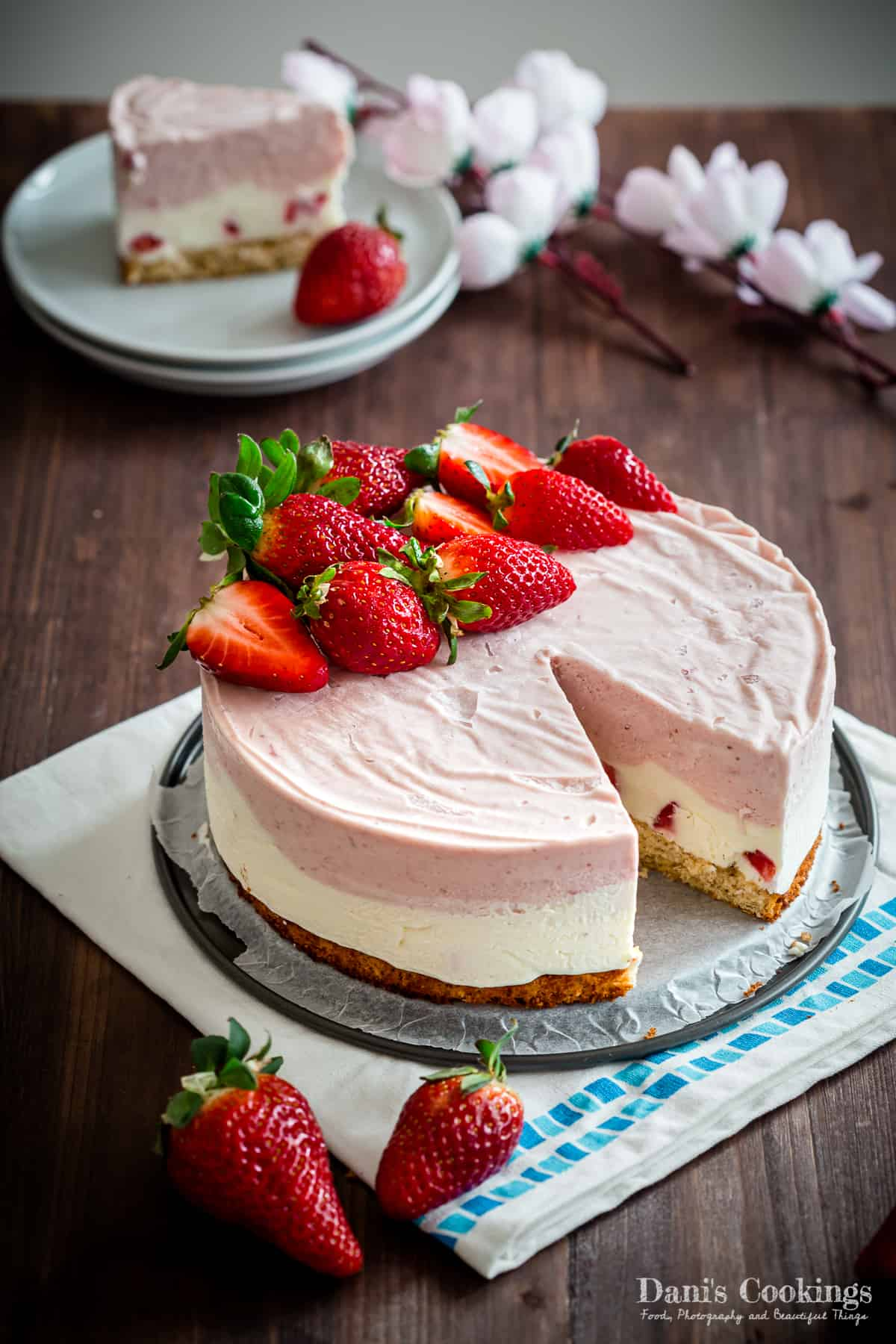 strawberry ice cream cake sliced on a wooden background
