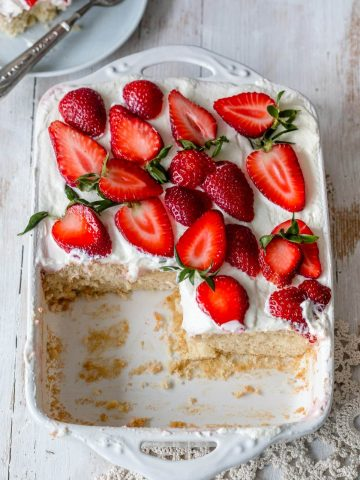 Strawberry Cheesecake Poke cake in a pan with few slices taken out