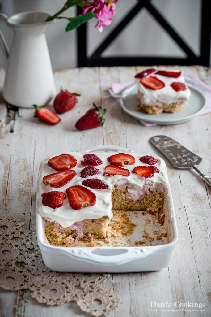 Strawberry Cheesecake Poke cake sliced and served on a wooden table