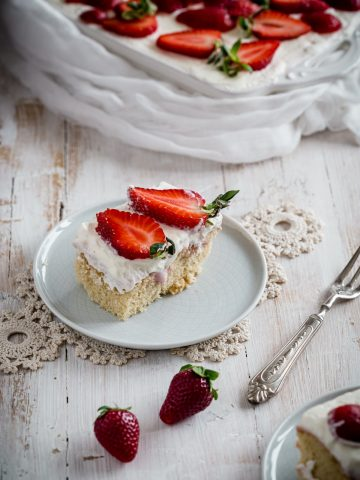 a slice of Strawberry Cheesecake Poke Cake on a plate