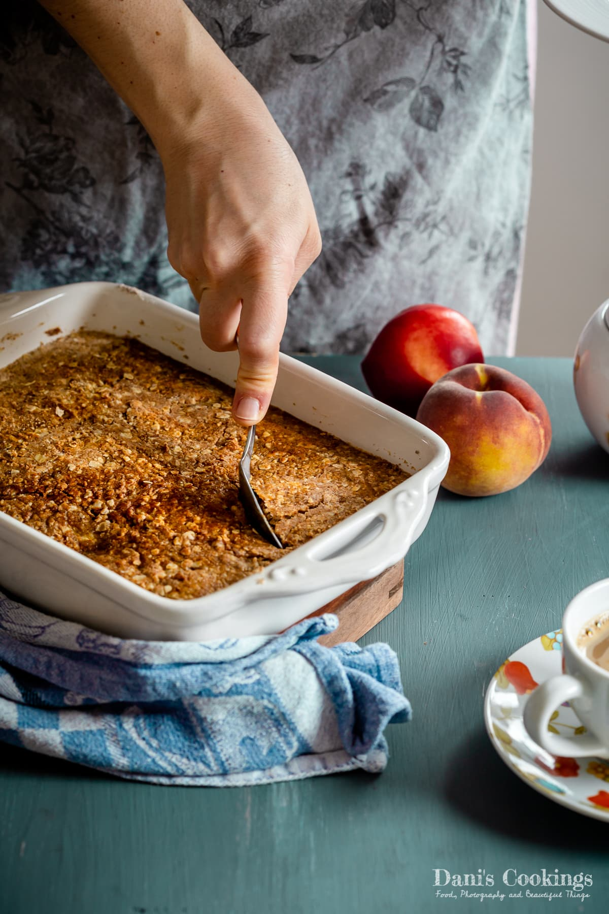 a woman taking from a peach dump cake with a spoon