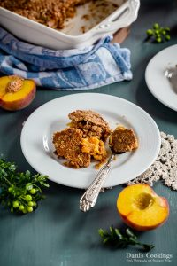 peach dump cake served on a white plate with a spoon and peaches aside