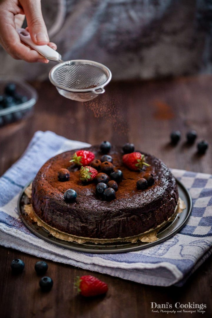 chocolate cake being sprinkled with cocoa