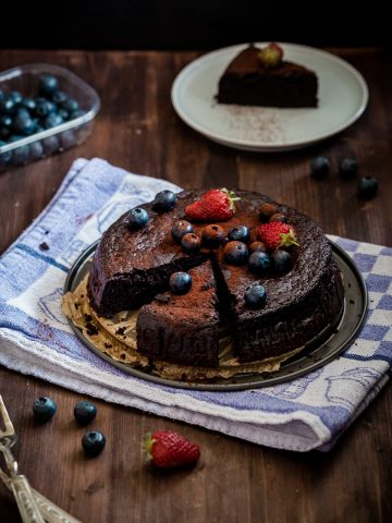 sliced chocolate flourless cake with berries