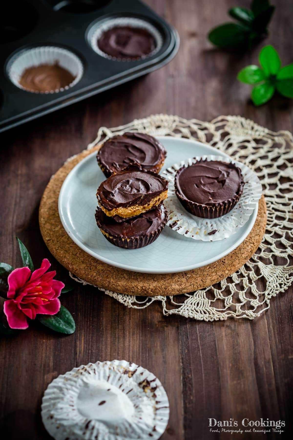 four peanut butter cups on a plate, one cut